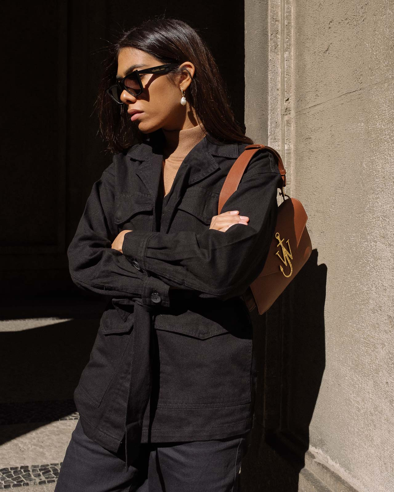 storm wears jw anderson bag with black edited jacket and beige turtleneck with old Céline sunnies and brown ganni boots