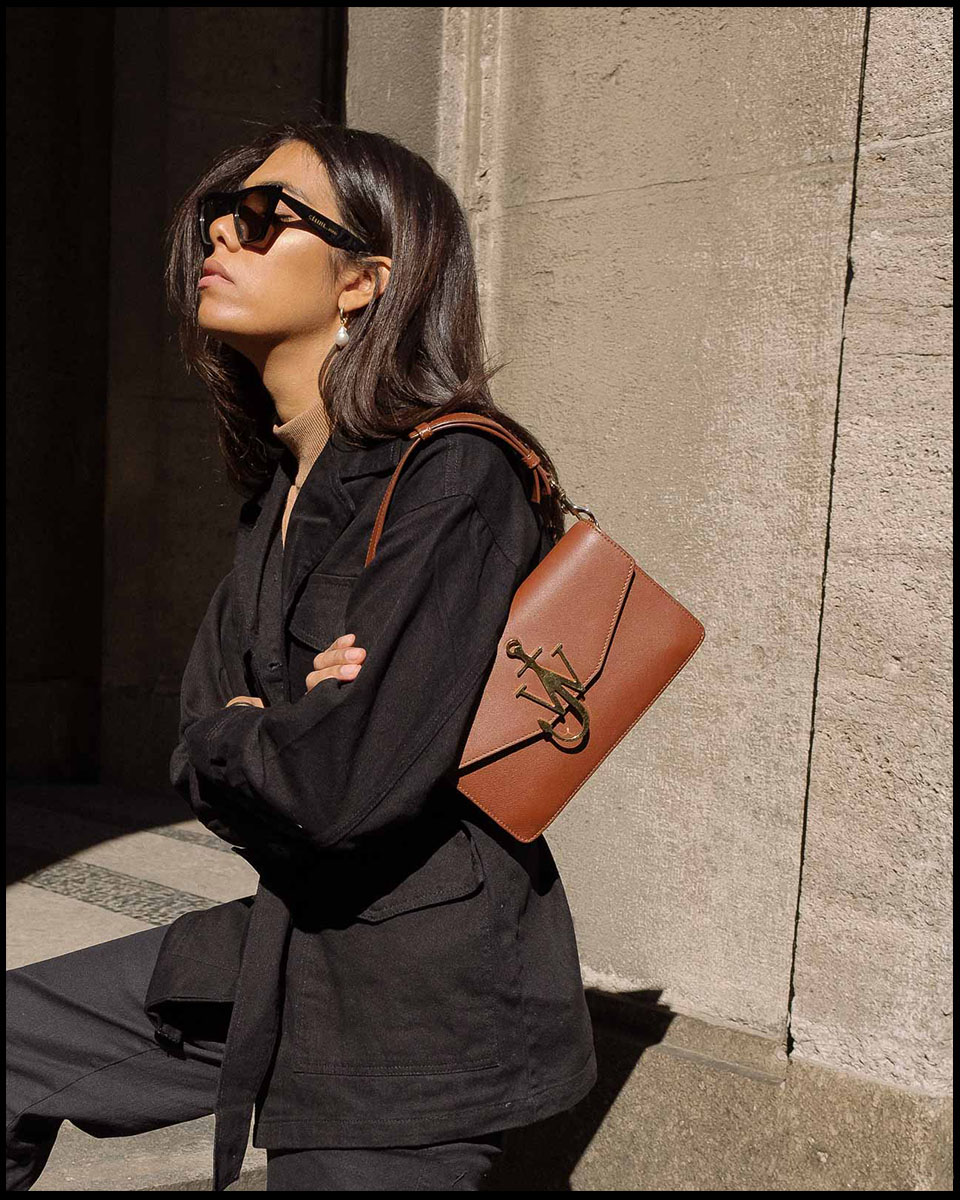 storm wears jw anderson bag with black edited jacket and beige turtleneck with old Céline sunnies