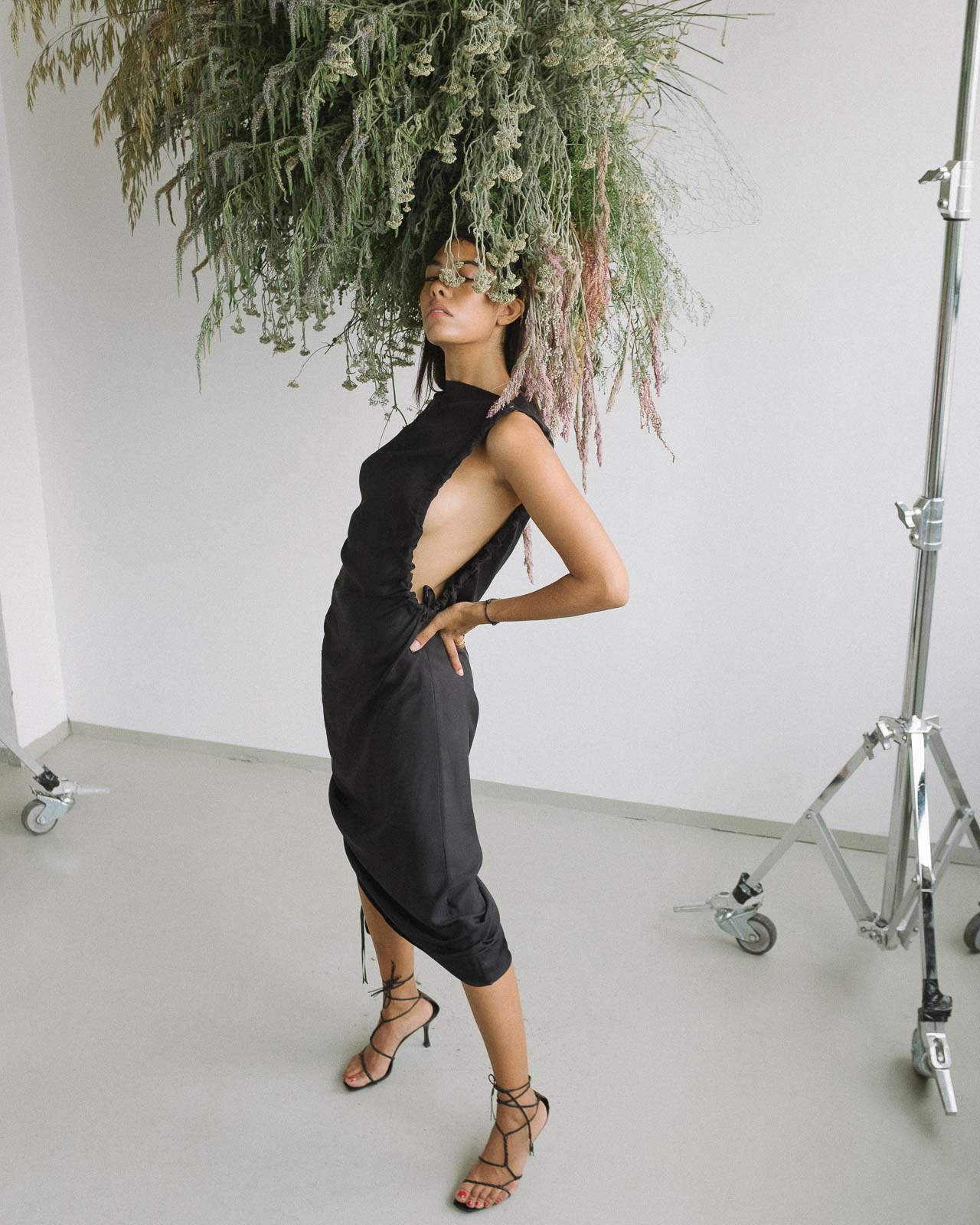 storm wears gucci vintage sandals with by malene birger black dress shot by marius knieling at studio230 flowers by studiolilo