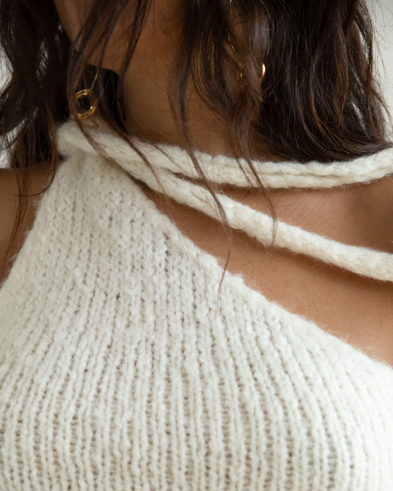 Storm wes wears malaika Raiss white knit top with gold earrings detail shot