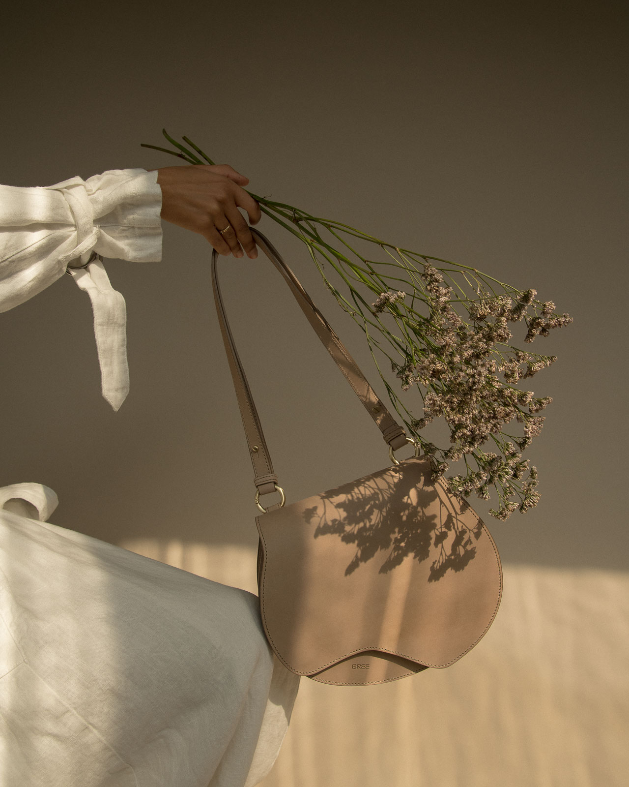 storm wears blanche copenhagen white linen coat with bree nature beauty bag in color humus shot by marius knieling