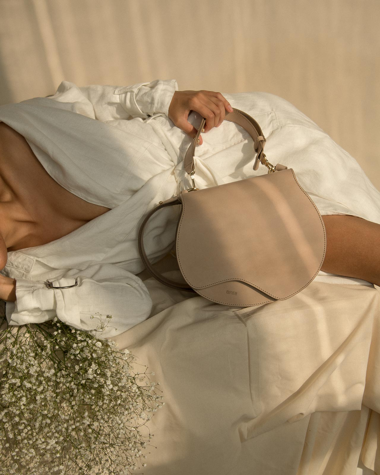 storm wears bree nature bag in the color hummus with a white blanche copenhagen linen coat at Studio230 shot by Marius Knieling