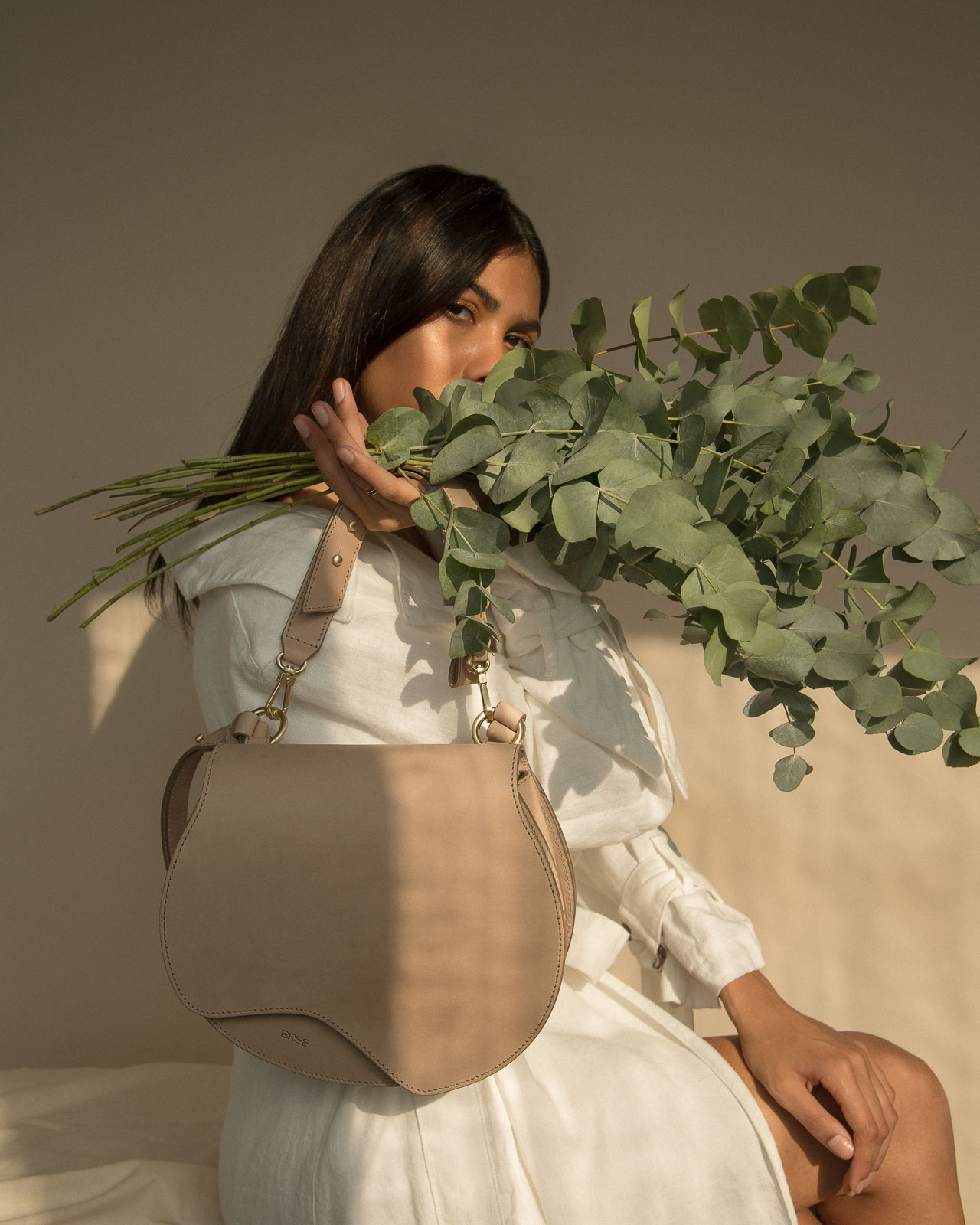storm wears bree nature bag in the color hummus with a white blanche copenhagen linen coat and eucalyptus at Studio230 shot by Marius Knieling