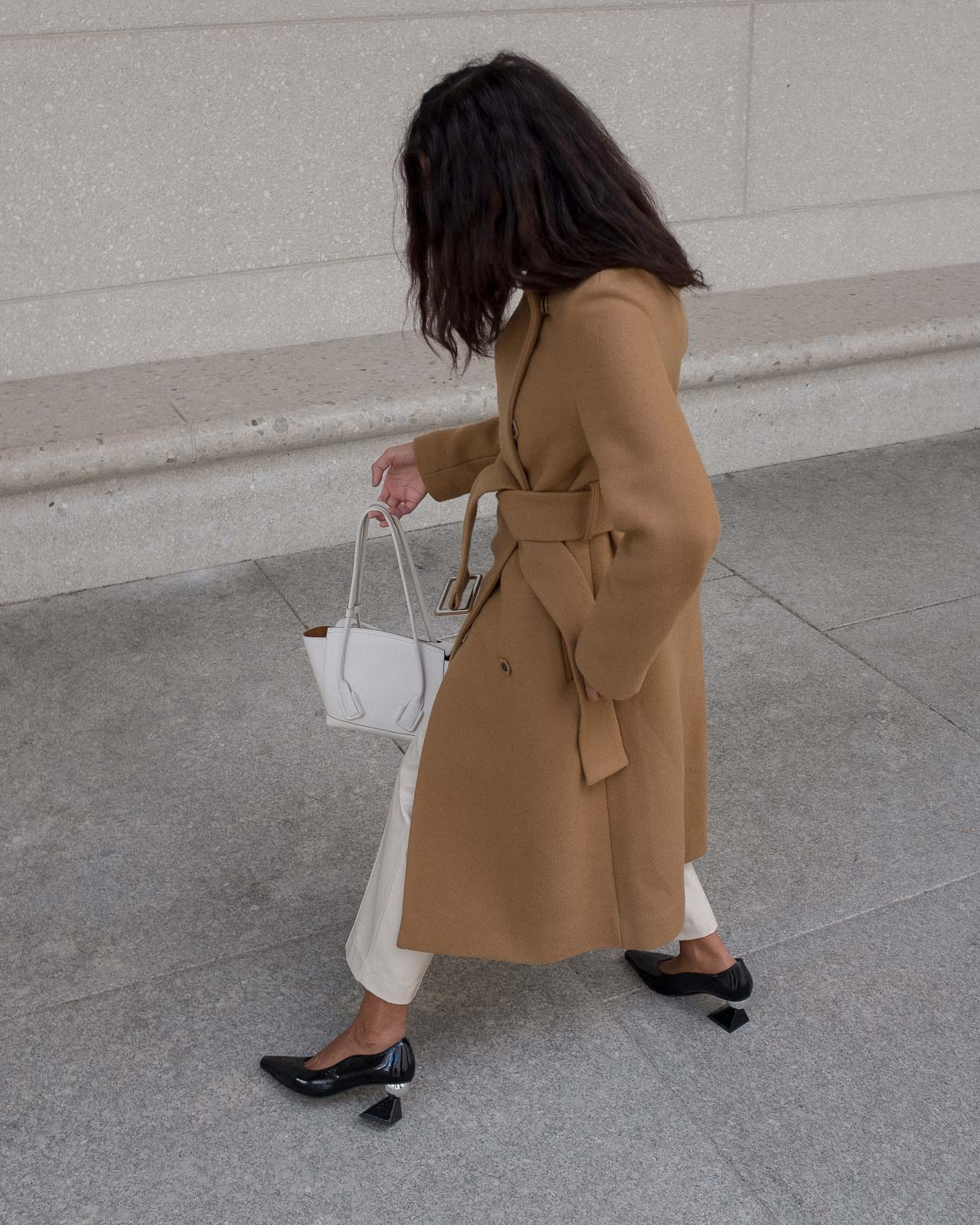 storm wears black mules from yuul yie combined with by malene birger camel coat and white arco bottega veneta bag