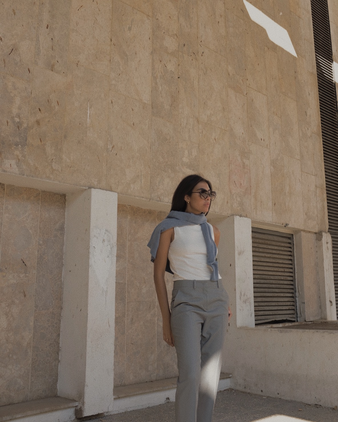 storm wears jake*s blue cashmere sweater with white top and grey pants in tel aviv jakes and the city