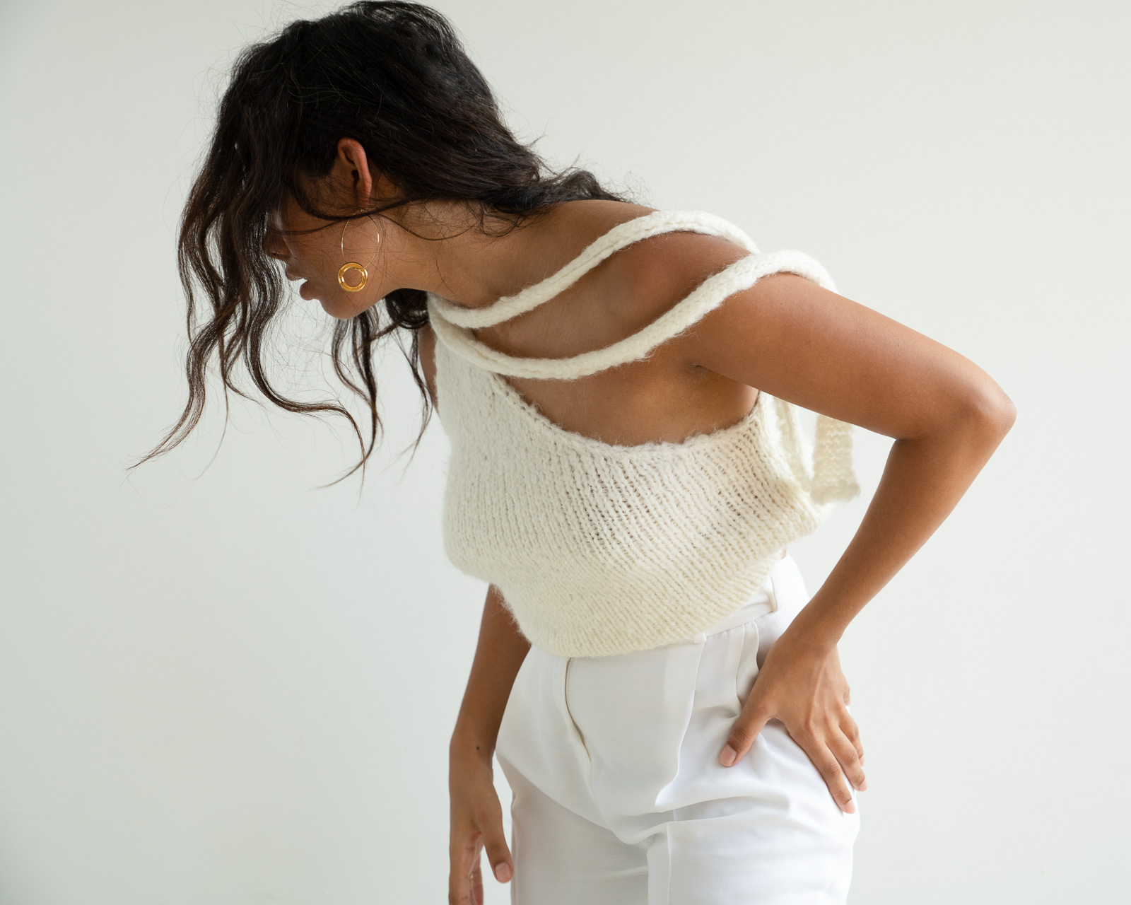Storm wes wears malaika Raiss white pants combined with knit top and gold earrings detail shot